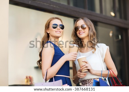 sale, consumerism and people concept - happy young women with shopping bags and coffee paper cups at shop window in city - stock photo