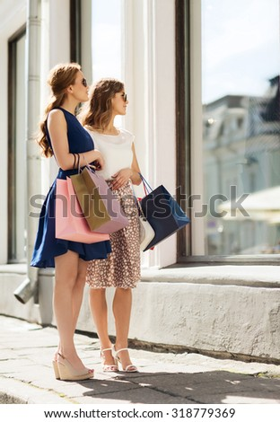 sale, consumerism and people concept - happy young women with shopping bags looking at shop window in city - stock photo