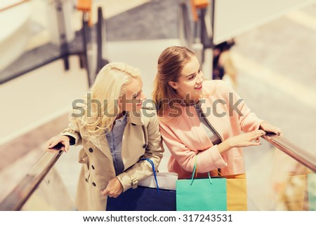 sale, consumerism and people concept - happy young women with shopping bags on escalator in mall - stock photo