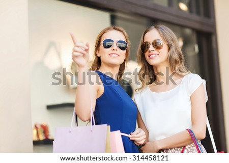 sale, consumerism and people concept - happy young women with shopping bags pointing finger at shop window in city - stock photo