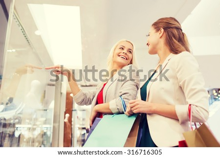 sale, consumerism and people concept - happy young women with shopping bags pointing finger in mall - stock photo