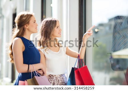 sale, consumerism and people concept - happy young women with shopping bags pointing finger to shop window in city - stock photo