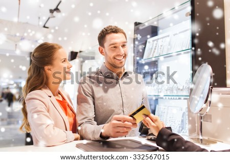 sale, consumerism, shopping and people concept - happy couple with credit card at jewelry store in mall with snow effect - stock photo