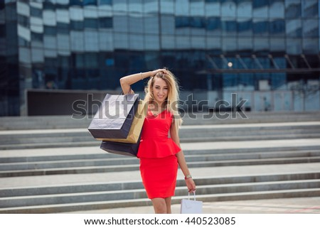 Sale, consumerism: Smiling young woman with shopping bags after mall - stock photo