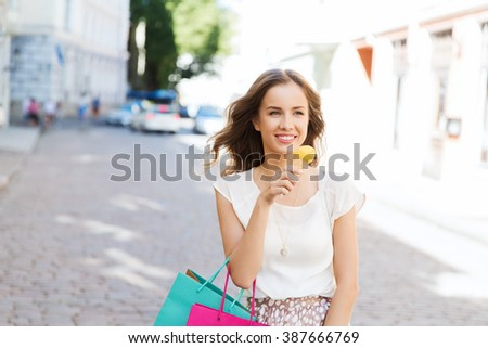 sale, consumerism, summer and people concept - happy young woman with shopping bags and ice cream on city street - stock photo