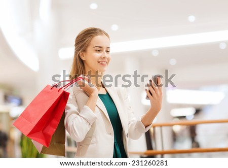 sale, consumerism, technology and people concept - happy young woman with smartphone and shopping bags taking selfie in mall - stock photo