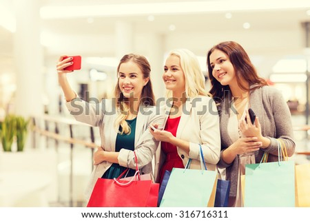sale, consumerism, technology and people concept - happy young women with smartphones and shopping bags taking selfie in mall