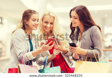 sale, consumerism, technology and people concept - happy young women with smartphones and shopping bags in mall - stock photo