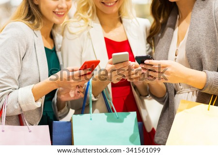 sale, consumerism, technology and people concept - happy young women with smartphones and shopping bags talking in mall - stock photo