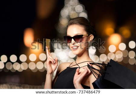 sale, fashion, people and luxury concept - happy beautiful young woman in black sunglasses with credit card and shopping bags over christmas tree lights background