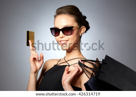 sale, finances, fashion, people and luxury concept - happy beautiful young woman in black sunglasses with credit card and shopping bags over gray background - stock photo