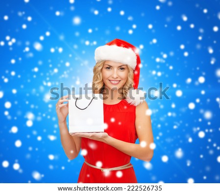 sale, gifts, christmas, holidays and people concept - smiling woman in red dress and santa helper hat with white blank shopping bag over blue lights background - stock photo