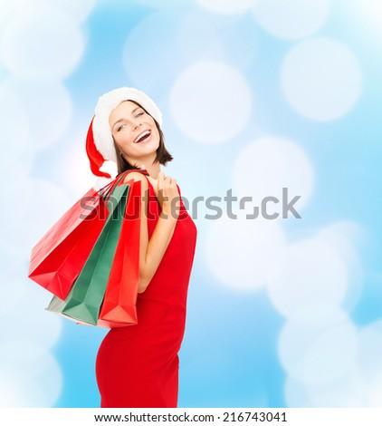 sale, gifts, christmas, holidays and people concept - smiling woman in red dress with shopping bags over blue lights background - stock photo