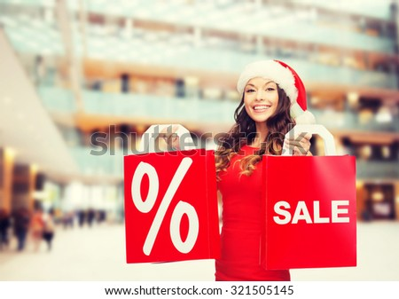 sale, gifts, christmas, holidays and people concept - smiling woman in red dress with shopping bags and percent sign on them over shopping center background - stock photo