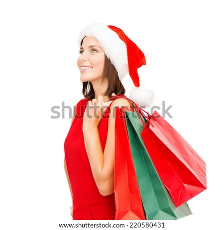 sale, gifts, christmas, x-mas concept - smiling woman in red dress and santa helper hat with shopping bags - stock photo
