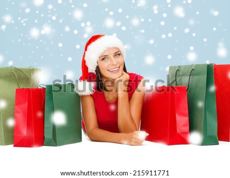 sale, gifts, christmas, x-mas concept - smiling woman in red shirt and santa helper hat with shopping bags - stock photo