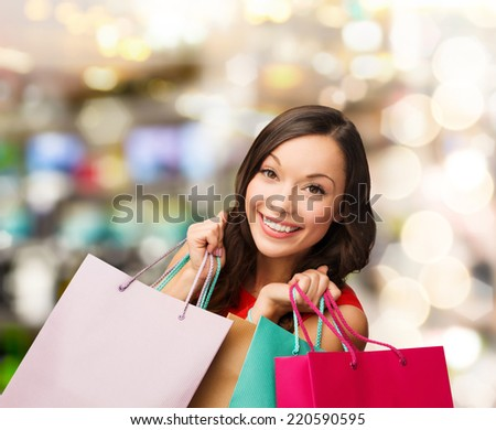 sale, gifts, christmas, xmas concept - smiling woman in red dress with shopping bags - stock photo