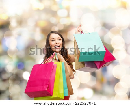 sale, gifts, holidays and people concept - smiling woman with colorful shopping bags over lights background