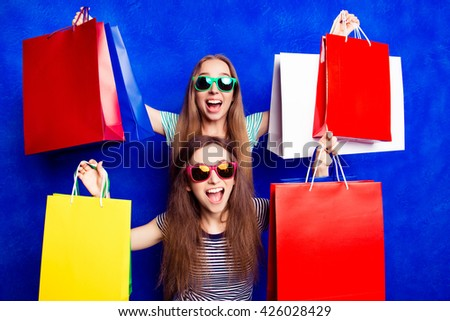Sale! Happy cheerful sisters showing their purchases - stock photo