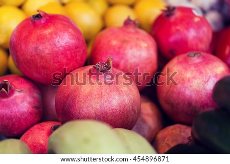 sale, harvest, food, fruits and agriculture concept - close up of pomegranate at street farmers market