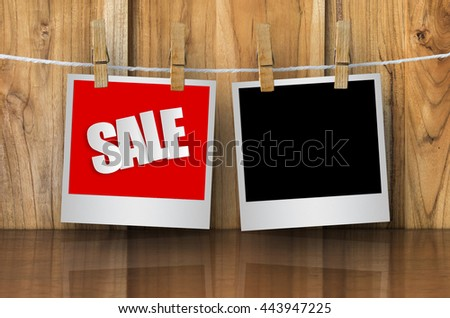Sale paper label in photo frame paper hanging on wooden background, discount banner. - stock photo