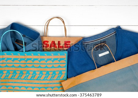 Sale. Paper shopping bags, men's shirts and tie on a white  wooden background. Space for text. Top view - stock photo