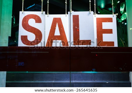 sale poster in fashion shop display window - stock photo