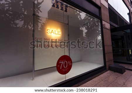 sale poster in the display window of shop - stock photo