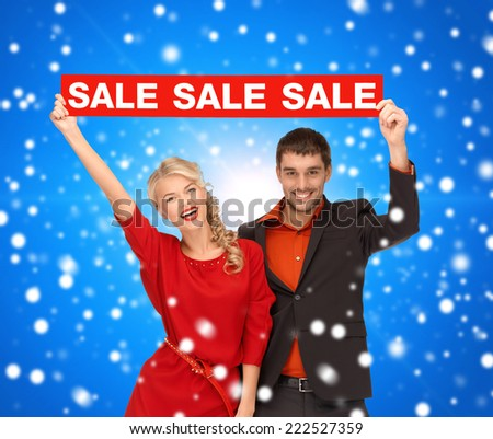 sale, shopping, christmas, holidays and people concept - smiling man and woman in red dress with red sale sign over blue snowing background - stock photo