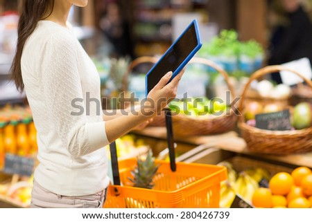 sale, shopping, consumerism and people concept - close up of young woman with food basket and tablet pc computer in market - stock photo