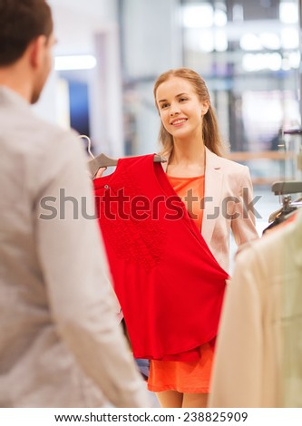 sale, shopping, consumerism and people concept - happy young couple choosing clothes at clothing store in mall - stock photo