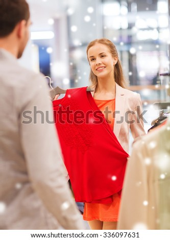 sale, shopping, consumerism and people concept - happy young couple choosing clothes at clothing store in mall with snow effect