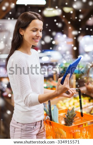 sale, shopping, consumerism and people concept - happy young woman with food basket and tablet pc computer in market over snow effect - stock photo
