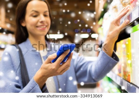 sale, shopping, consumerism and people concept - happy young woman with smartphone choosing and buying food in grocery store or market over snow effect - stock photo