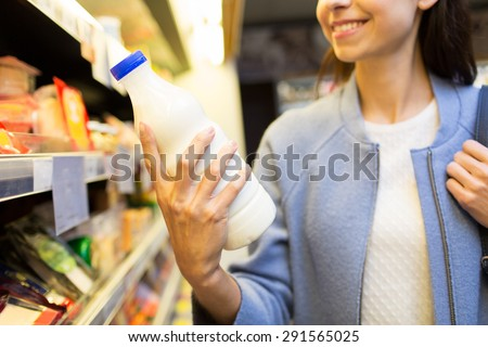 sale, shopping, consumerism, food and people concept - close up of happy young woman holding milk bottle in market - stock photo