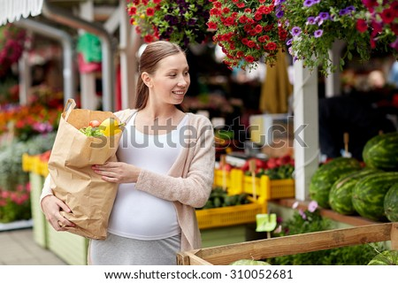 sale, shopping, pregnancy and people concept - happy pregnant woman with paper bag full of food at street market - stock photo