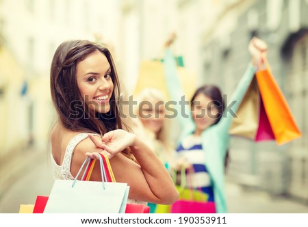 sale, shopping, tourism and happy people concept - beautiful woman with shopping bags in the ctiy - stock photo