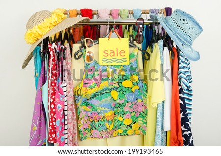 Sale sign for summer clothes. Clearance rack with colorful summer outfits and accessories displayed on hangers. - stock photo