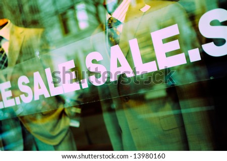 Sale sign on glass window of fashion boutique - stock photo