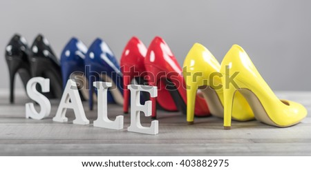 Sale sign with high heels shoes set on grey background