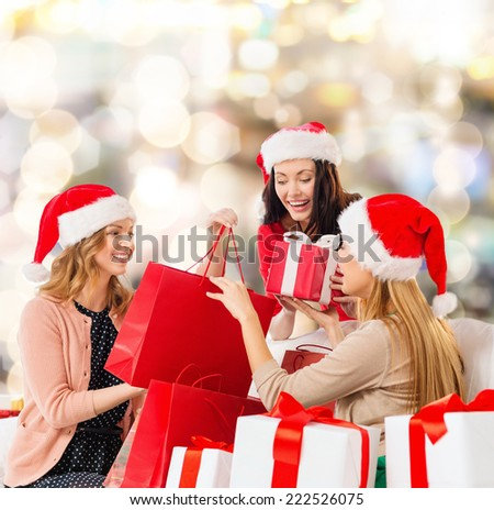 sale, winter holidays, christmas and people concept - smiling young woman in santa helper hat with gifts and shopping bags over lights background - stock photo