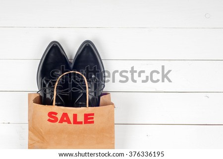Sale with shoes on wooden background - stock photo