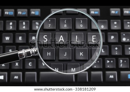 SALE written on keyboard with magnifying glass