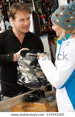Sales Assistant Helping Advising Female Customer On Ski Boots In Hire Shop - stock photo