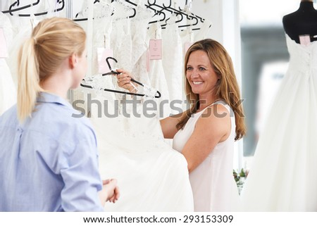 Sales Assistant In Bridal Store Helping Bride To Choose Wedding Dress - stock photo