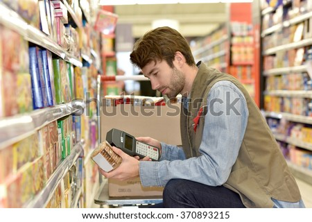 Sales assistant scanning products before putting for sale - stock photo