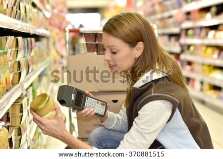 Sales assistant scanning products before putting them on shelves - stock photo