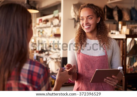 Sales Assistant With Credit Card Reader On Digital Tablet - stock photo