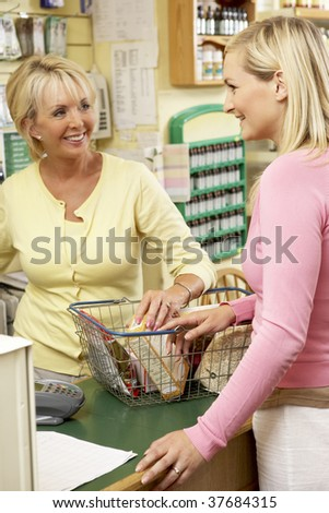 Sales assistant with customer in health food store - stock photo