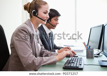 Sales assistants working with computers in an office - stock photo